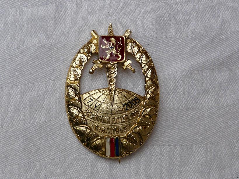 Lícová strana odznaku Bojovník rozhlasu, který byl vyroben přesně dle původní předlohy z roku 1945. Odznak dostalo 100 vybraných účastníků rekonstrukce boje o rozhlas.